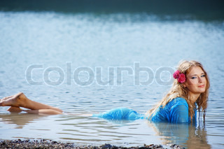 Portrait of young beautiful woman resting in water