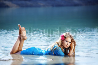 Portrait of young beautiful woman posing in water