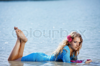 Portrait of young beautiful woman lying in water