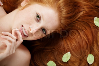 Beautiful woman with red hair and leaves on it lying on wooden floor in spa salon