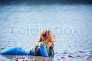 Portrait of young beautiful woman resting in water with rose petals
