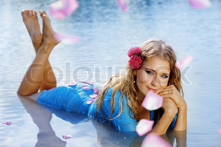 Portrait of young beautiful woman resting in water with flying rose petals