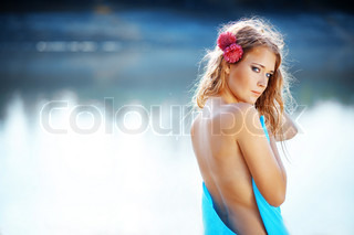 Portrait of young beautiful woman posing near lake