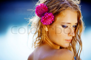 Portrait of young beautiful smiling femaleover blue lake water