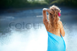 Portrait of young beautiful woman posing near lake back view