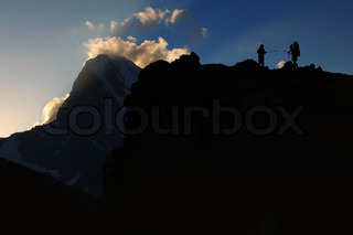 Mountain sport - silhouette of two climbers in high mountain pass
