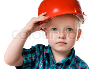 little boy in a red construction helmet on white background