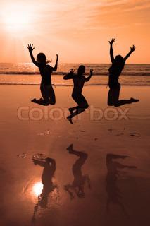 drei Personen Silhouetten springen am Strand