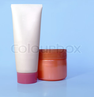 Cosmetic tube and pot of cream on light blue background, blank for applying new branding