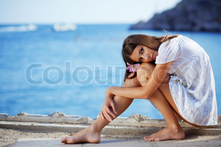 Portrait of beautiful brunette woman with long legs posing over sea view