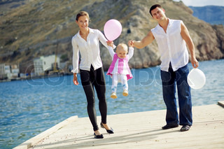 Portrait of happy young family walking with their child on berth near sea