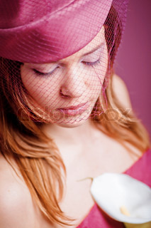 Soft portrait of woman in hat with veil closeup in pink color