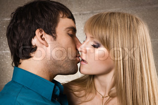 Young romantic couple kissing in house interior