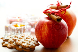 Close-up of delicious red Christmas apples with cinnamon sticks, gingerbread cookies and candles