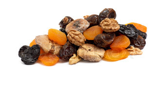 Heap ofdifferent dried fruits and walnuts isolated on a white background