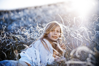 Girl lying in field of feather grass in soft evening sunshine