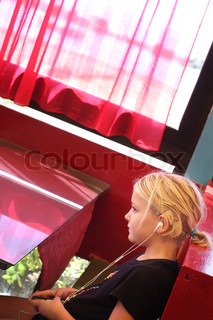 a young girl, teenager, listening to music though earplugs in a bar High contrast image, shot in angular way