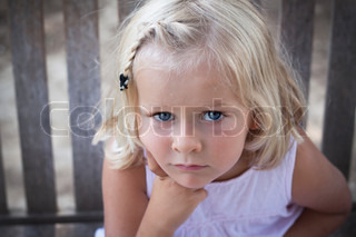 A 5 year old child looking seriously at the camera Soft focus on background