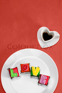 Candies spelling love with heart-shaped coffee cup