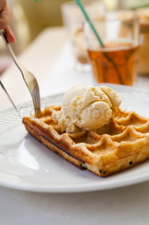 Delicious waffle with vanilla ice cream on a restaurant table