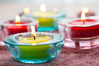 Close-up of yellow and red candles in glass holders on pink sand