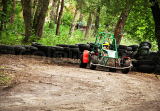 homemade buggy on earthen track with barrier of tires on trees background