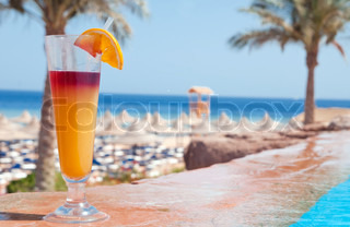 A glass of alcohol fruit cocktail at the pool near sea