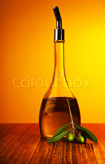 Homemade healthy olive oil, fresh green olives and bottle of oil over yellow background, salad dressing, harvest and organic food concept
