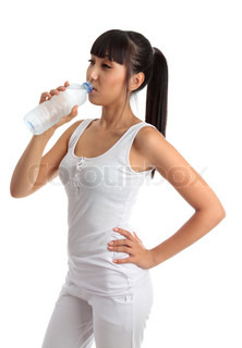 A young beautiful girl wearing white gym clothes is drinking refreshing water from a clear plastic bottle