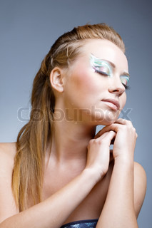 Fashion model with ceremonial make-up and face-art on blue studio background