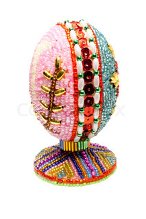An easter egg is decorated a bead on a white background