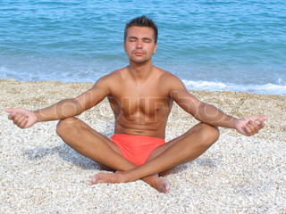 Young man in a meditation on the beach in position Lotus