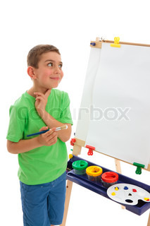 A young boy child stands by his easel and contemplates what do paint
