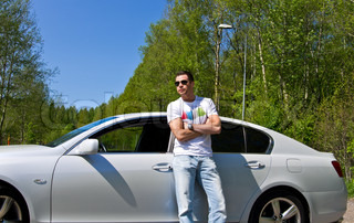 Young man standing near his car