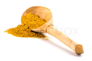 pile of yellow turmeric on wooden spoon on white background