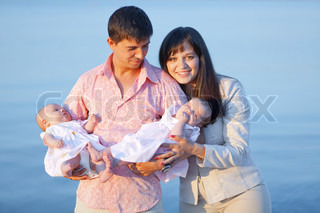 Happy young family with infant children over sea