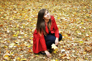 beautiful young girl picks up the maple leaves in autumn park