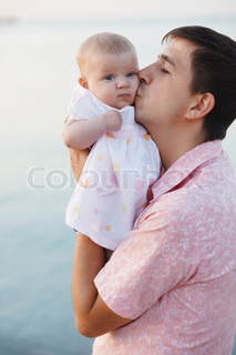 Young father kissing his infant baby