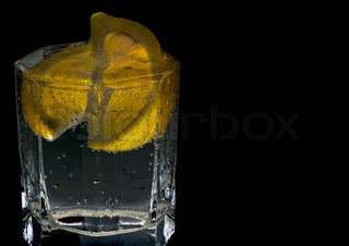 glass with soda water and lemon slices on black background