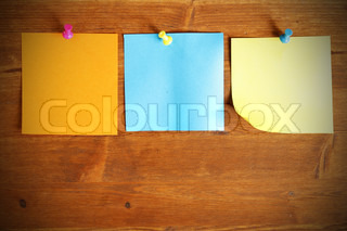 Three colorful blank note papers attached to a wooden wall