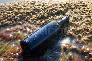 Wine in the bottle lying on the beach