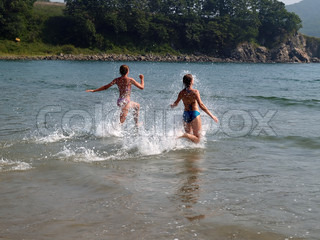 young girls running to the sea