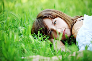 Young cute girl resting in fresh grass