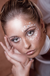 Fashion model with delicate make-up and face-art close-up