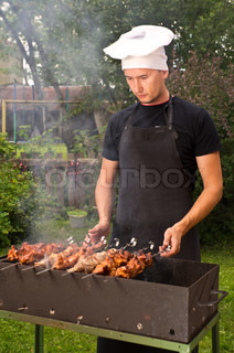 Man cook grilling meat on coal in brazier