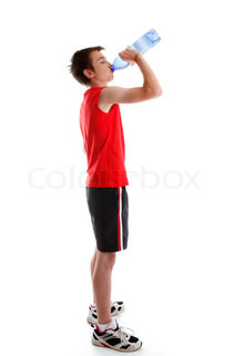 A teenage boy dressed in sports wear is drinking water from a bottleWhite background