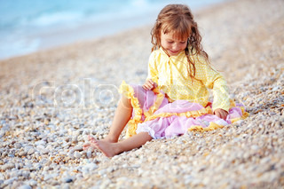 Little girl playing at the autumn beach