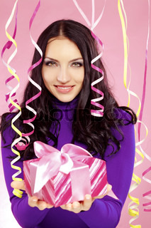 Portrait of beautiful woman with holiday paper streamer and gift