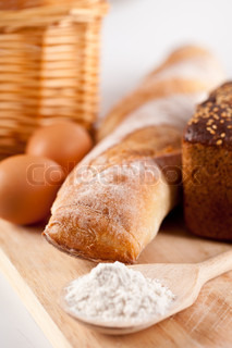 still life of bread, flour, eggs and kitchen utensil on a wooden board