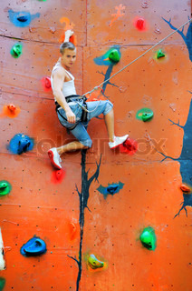 man climbing on a climbing wall training in insurance
